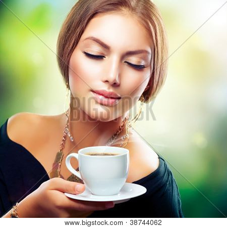 Tea. Beautiful Girl Drinking Tea or Coffee. Healthy Beverage. Woman with Cup over Nature Green Background