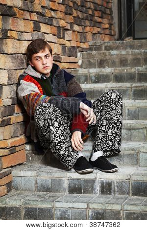 Young hippie man sitting on the steps