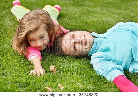 Happy woman and girl lie in autumn park