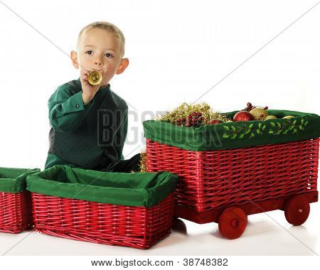 "An adorable preschooler blowing a toy trumpet by a red wicker ""basket train"" filled with Christmas decor.  On a white background."