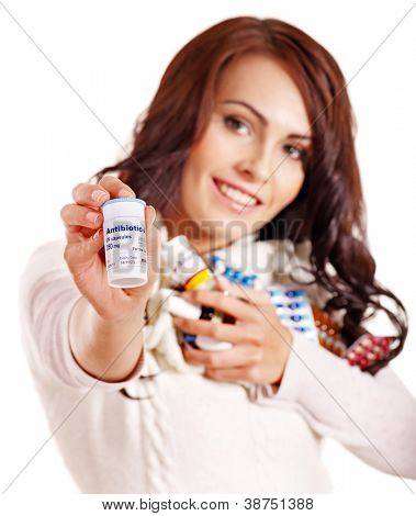 Young woman having pills and tablets. Focus is the bottle with the medicine. Isolated.