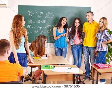 Estudiante feliz del grupo en el aula junto a la pizarra.