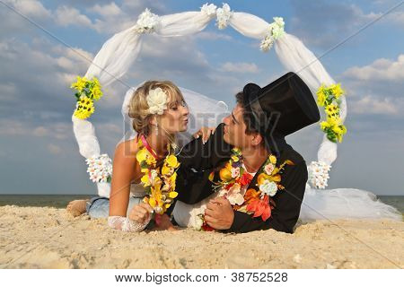 Groom with bride wearing lei lying on beach