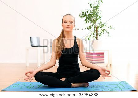 Young and beautiful woman meditate at home on blue mat
