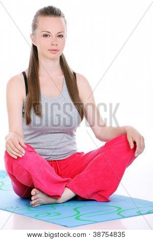 young and cute woman meditate on a blue mat isolated on a white