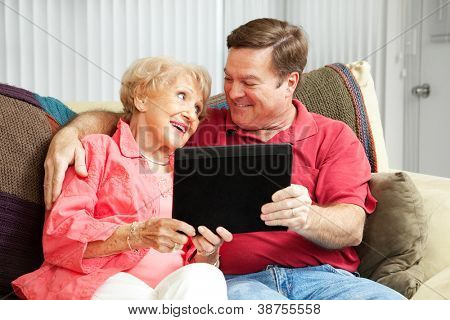 Adult son teaching his elderly mother how to use her new tablet PC.