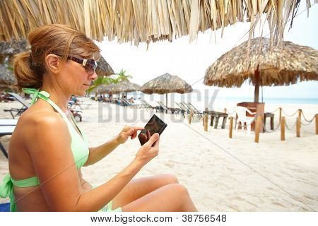 Woman with a smartphone on the beach. Vacation.
