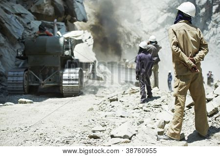 indian asian site manager engineer builder inspecting road  clering at mountains construction site