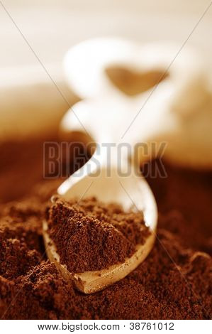 ground coffee powder in heart shape wooden spoon, shallow dof