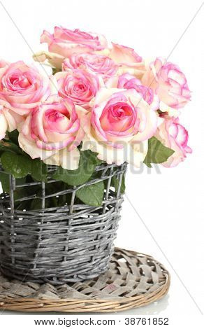 beautiful bouquet of pink roses in wicker vase, isolated on white