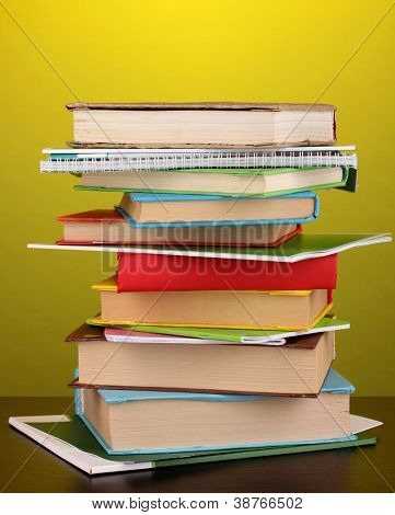 Stack of interesting books and magazines on wooden table on yellow background