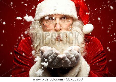 Foto do Papai Noel em óculos de neve de sopro e olhando para câmera
