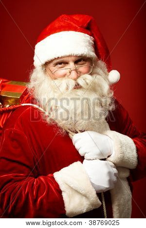 Portrait of happy Santa Claus holding sack with gifts and looking at camera