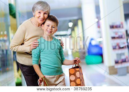 Retrato de criança feliz, segurando a paperbag com sua avó perto por