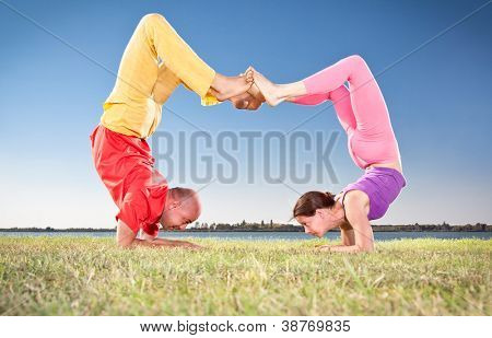 Yoga couple, man and woman doing Vrschikasana scorpion pose on lake bench. Yoga concept.