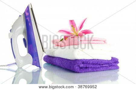 Pile of clothes with lily and electric iron, isolated on white