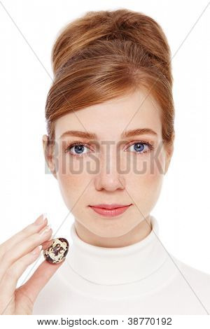 Young red-haired girl with freckles holding quail egg in her hand, on white background