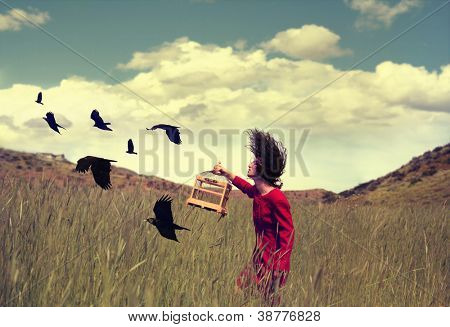 a girl walking through a field with a flock of ravens or crows