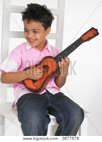 An Adorable Asian Boy Playing A Toy Guitar