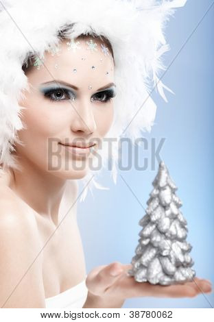 Winter beauty holding small pinewood in hand, wearing luxurious makeup and white feather hat.