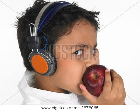 Boy Eating A Red Apple And Listening To Music