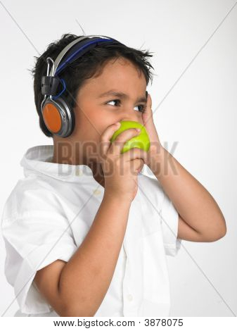 Asian Boy Eating A Green Apple And Listening To Music