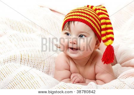 cute baby lying on pink plaid and smiling in vivid funny hat, beautiful kid's face closeup with copyspace