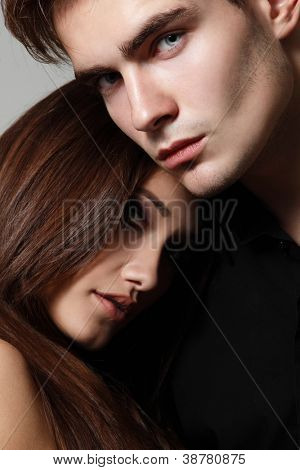 Sexy couple, beautiful young female and male faces closeup, studio shot