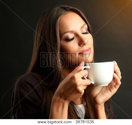 beautiful young woman with cup of coffee, on brown background