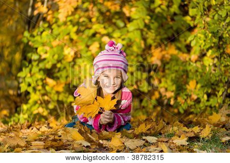 portrait of a pretty little girl against autumn leaves