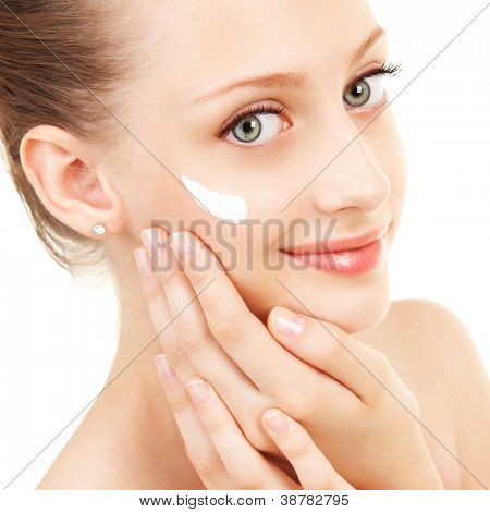 Cute woman applying cream to her face