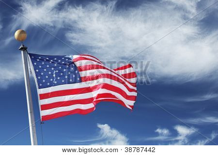 USA. Windblown flag of the United States of America over sky background.