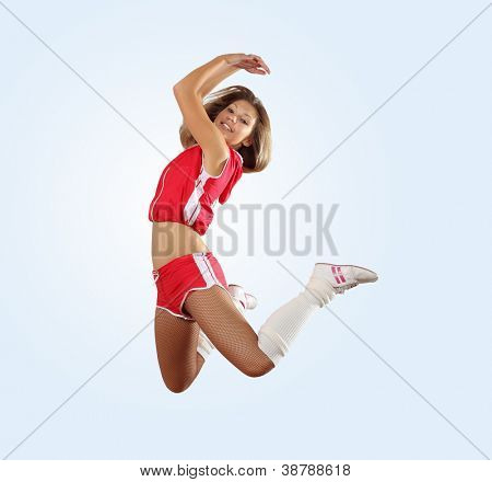 Uniformed cheerleader jumps high in the air isolated on white.