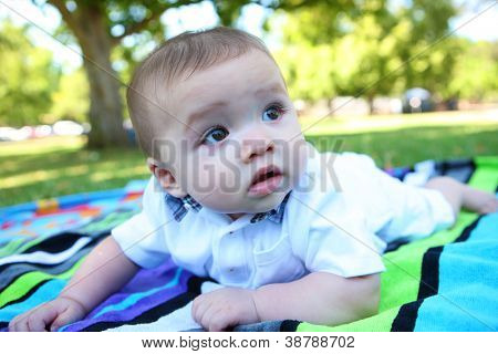 A cute baby boy laying in the park