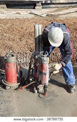Builder in helmet tightens screws in damp concrete foundation.