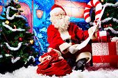 stock photo of nicholas  - Santa Claus posing with a list of presents over Christmas background - JPG