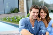 image of 35 to 40 year olds  - Cheerful couple sitting in front of new house - JPG