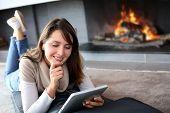 Woman using digital tablet laying by fireplace
