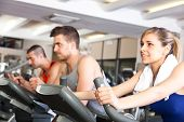 stock photo of pedal  - Happy people doing indoor biking in a fitness club - JPG