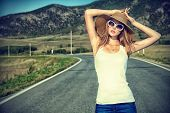 image of independent woman  - Beautiful young woman posing on a road over picturesque landscape - JPG