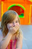 Blond kid girl funny gesture hand in mouth in playground with sundress