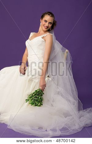 beautiful bride in ivory chiffon dress with lace and long tule veil sitting  against purple studio background