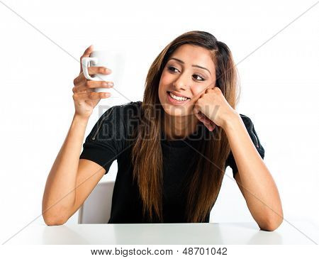 Attractive young asian indian woman enjoying a drink