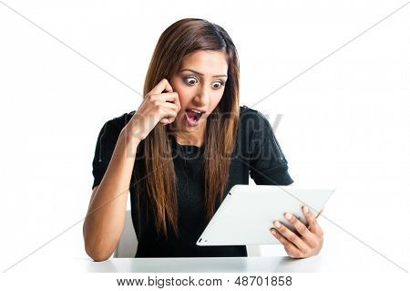 Attractive young Asian Indian teenage woman, working with a non-branded generic portable tablet looking quite shocked