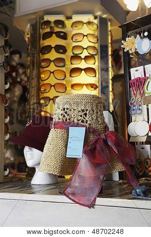 Closeup de sombreros y gafas de sol en pantalla tienda de segunda mano
