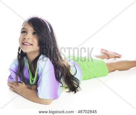 A beautiful elementary girl looking up as she lays on her belly in casual, summer clothes.  On a white background.