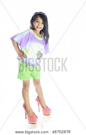 A beautiful young elementary girl smiling while she struggles to balanance in her mother's super high heals.  On a white background.