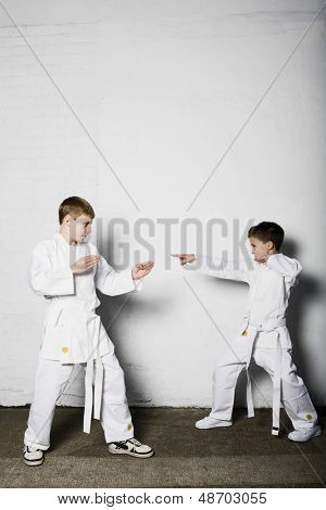 Full length of two young boys practicing judo