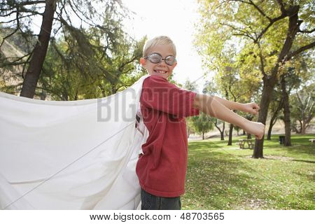 Side view of a young boy wearing cape and swimming goggles outdoors