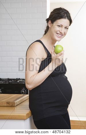 Portrait of a happy pregnant woman eating apple in the kitchen